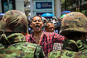 "25 MAY 2014 - BANGKOK, THAILAND: A Thai ""Red Shirt"" supporter of the ousted civilian government confronts soldiers at a demonstration against the military junta. Public opposition to the military coup in Thailand grew Sunday with thousands of protestors gathering at locations throughout Bangkok to call for a return of civilian rule and end to the military junta.     PHOTO BY JACK KURTZ"