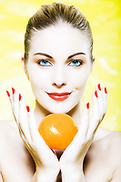 beautiful caucasian woman portrait holding an orange studio on yellow background