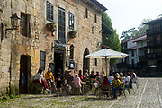 SANTILLANA DEL MAR, SPAIN - April 20 2018 - Tourists enjoy food and drinks on sunny day outside tapas restaurant in town centre of Santillana del Mar, Cantabria, Spain.