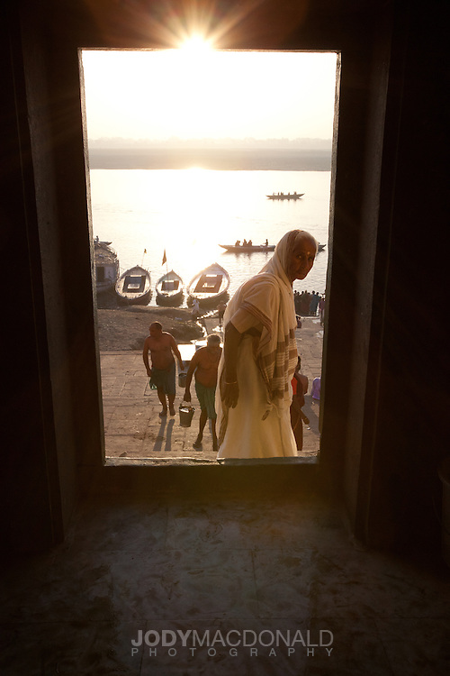 Looking out through a window at sunrise on the Ganges river with bent woman in frame looking at camera