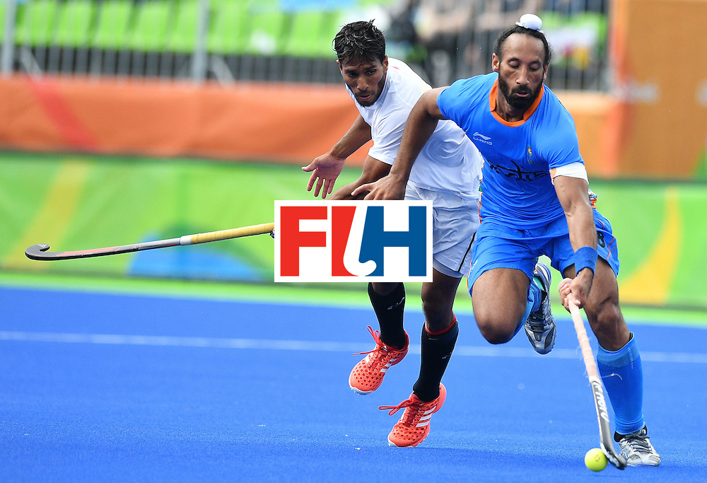 Canada's David Carter (L) and India's Sardar Singh vie during the mens's field hockey India vs Canada match of the Rio 2016 Olympics Games at the Olympic Hockey Centre in Rio de Janeiro on August, 12 2016. / AFP / Carl DE SOUZA        (Photo credit should read CARL DE SOUZA/AFP/Getty Images)