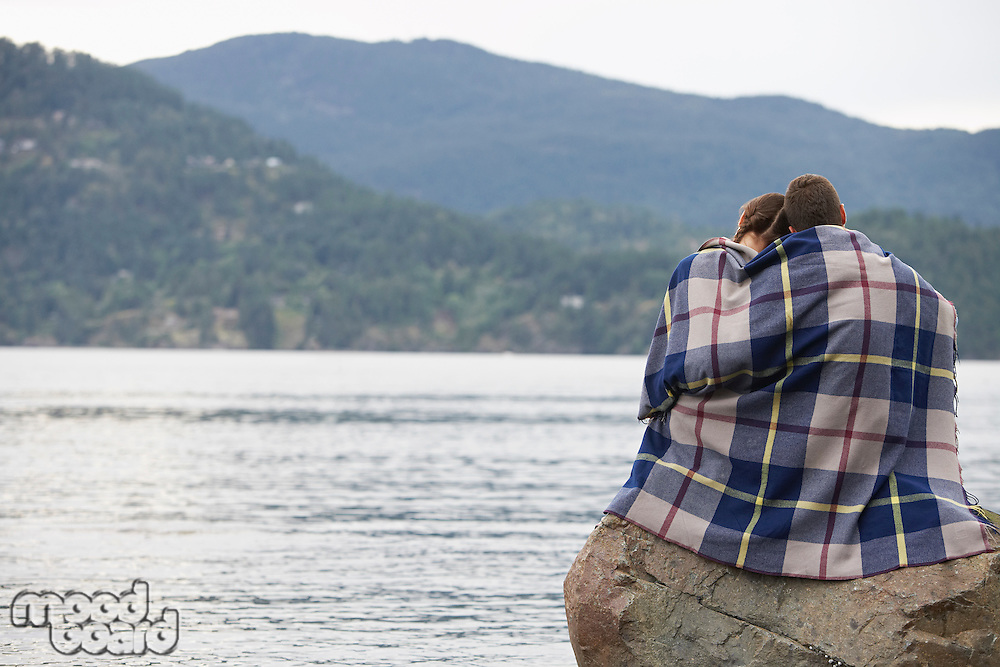Couple wrapping in blanket sitting on rock by ocean