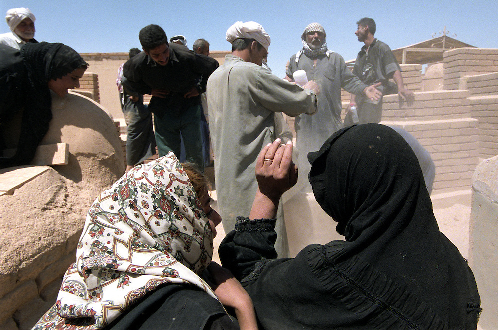 The family of Selman Khalaf bury his 18 year old son Ahmed Selman Khalef in the sacred Shiite burial ground after he was shot by US forces at a check point near Baghdad while riding in a car with his father..Najaf, Iraq. 02/05/2003..Photo © J.B. Russell