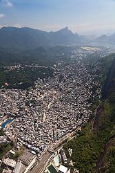 Rio de Janeiro visto de cima.Rocinha e Zona Sul. A Rocinha eh um bairro-favela localizado na cidade do Rio de Janeiro, no Brasil. Destaca-se por ser uma das maiores favelas da cidade, contando com cerca de 60 mil habitantes..Eh vizinha a um shopping center, entre os bairros da Gavea e de Sao Conrado, dois dos bairros com o IPTU mais alto da cidade. A proximidade entre as residencias de classe alta desses dois bairros e as de baixa e pobre da Rocinha marca um profundo contraste urbano na paisagem da regiao / Rocinha is the largest favela in Rio de Janeiro. It is located in Rio's South Zone, between the districts of Sao Conrado and Gavea. It is built on a steep hillside overlooking the city, just one kilometre from the beach.