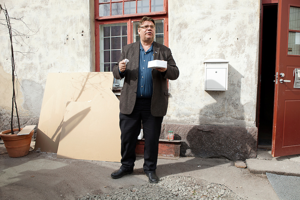 Timo Soini takes a break and enjoyes a cake outside the party office under construction in Lappenranta.