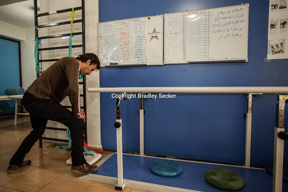 An injured man stretching in a post-care centre in the Turkish border town of Reyhanli. 04/01/2013