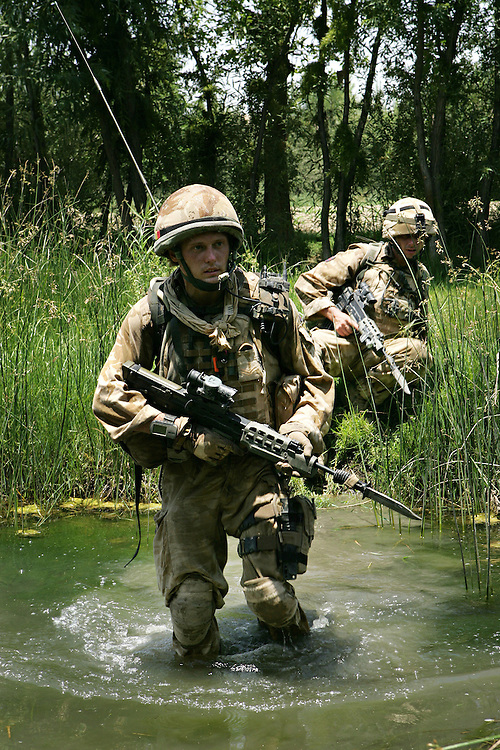 29/06/07..Sangin Valley, Helmand, Afghanistan..Soldiers from A Company 1 Battalion Royal Anglians, known as 'The Vikings' with fixed bayonets wade through irrigation canals whilst conducting operations against the Taliban in the Sangin Valley, Helmand province, Afghanistan on the 29th June 2007...The soldiers made a Tactical Advance to Battle over night carrying just food, water and ammunition. At first light they moved on their objectives; a series of compounds, orchards and paddy fields. During the day they exchanged fire with the enemy on a number of occasions. 13 Taliban were killed, 1 British soldier and 3 Afghan troops were wounded.
