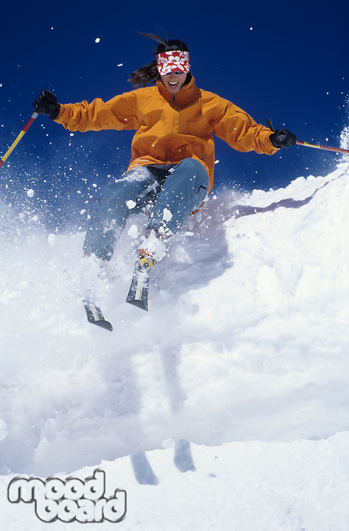 Skier skiing through snow jumping from snow bank