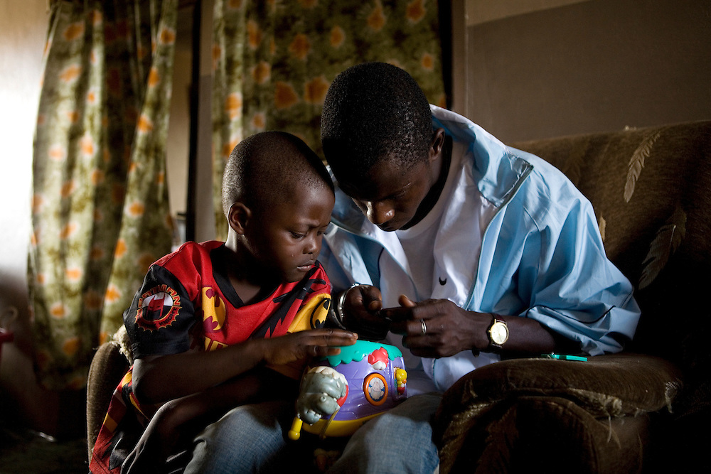Mommy's boyfriend Usman and son Rahim. Usman helps Rahim fix his toys. ..Mommy delivered and died from postpartum bleeding at the PCMH (Princess Christian Memorial Hospital). Freetown, Sierra leone.