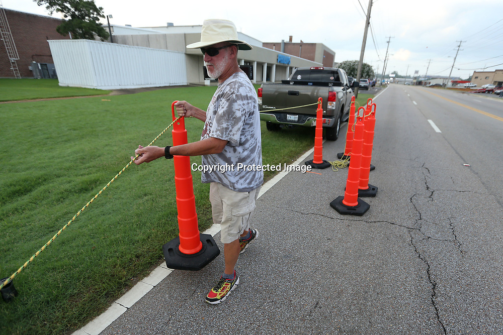 David Whiteside, of Pontotoc, sets up the cones for the finishline before the start of the Green Street Mile Run Tuesday morning in Tupelo.