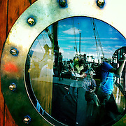 Passengers reflected in a door window on the TSS Earnslaw, the 100 year old vintage coal fired passenger steam ship which sails on Lake Wakatipu, Queenstown, New Zealand. The popular tourist attraction is celebrating it's centenary year with celebrations planned for October 2012.  Queenstown, Central Otago, New Zealand. 29th February 2012. Photo Tim Clayton