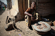 A woman sells shrimp on a street corner.  The slum of Cheetah Camp on the outskirts of Mumbai, India is a predominantly muslim community on living on the fringe while the city continues to grow.