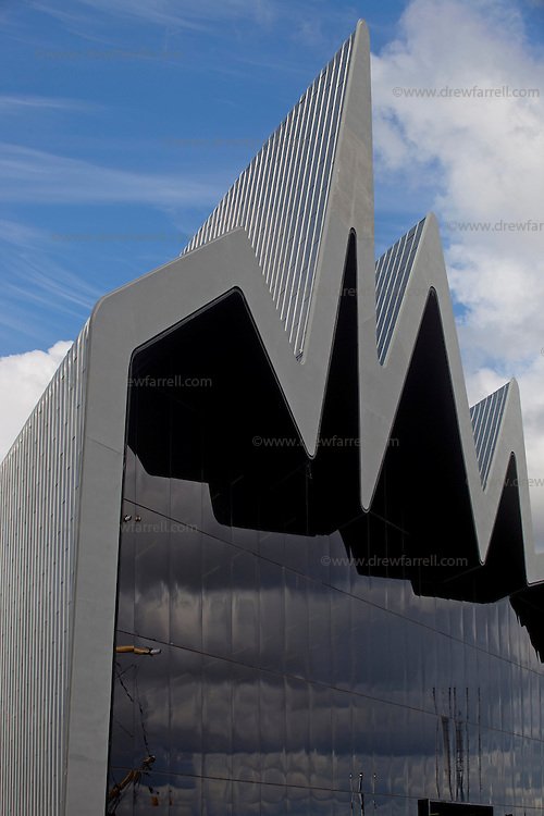Zaha Hadid's Riverside Museum. Glasgow, Scotland, UK..Press Launch with Architect Zaha Hadid..Glasgow's new waterfront home for the city's unique collection of transport , engineering and shipbuilding legacy which made Glagow great . Designed by Iraqi architect Zaha Hadid. This is her first major public commission to open in the UK. The  seventy four million pound glass and zinc clad museum stands beside the River Clyde and  is able  to house over 3,000 items from the collection inside the pistachio coloured interior. Vintage cars sit alongside steam locomotive engines, diesels, bikes and skateboards.  Three walk through  1900s street scene gives visitors a flavour of  a bygone Glagow and over 150 interactive displays telling the stories of the people  who made the term 'Clyde Built' brings the experience up to date.  It also houses the city's unrivalled  ship model collection.   Outside, the refitted Tall Ship Glenlee is moored in front of the  museums dramatic south facade.  After getting the go-ahead in 2002, work on-site at the historic Pointhouse Quay, began in 2007, with  the main contractors BAM, using 2,500 tonnes contructing the roof , without any internal supporting columns  in a feat of  architectural  engineering innovation. The Museum opens to the public on the 21st June 2011..Picture Drew Farrell.Friday 10th June 2011.