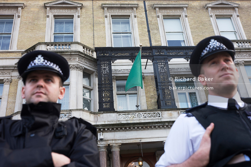 London Metropolitan police officers guard the outside of the London Libyan embassy that still flies the pro-Gadaffi flag.