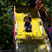 Adults and children on the slide during the May Fair at Saint Mark's Church, New Canaan, Connecticut, USA. 12th May 2012. Photo Tim Clayton