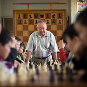 High-school students attend compulsory chess class in Elista, capital of the southern Russian republic of Kalmykia...The province is run by President Kirsan Ilyumzhinov, 44, who is a millionaire businessman and chess fanatic. He made chess compulsory in all schools. ..Ilyumzhinov, also the president of Fide, the World Chess Federation, is hosting the world?s most important match in September 2006. ..The match, beginning September 21 in Elista, will end a 13-year split in the game that has produced rival claims to the title. ..Veselin Topalov, a Bulgarian ranked first according to Fide, will play against Vladimir Kramnik, who is the Classical Chess World Champion, a title established after Garry Kasparov led a breakaway from Fide in 1993. The two grandmasters, both aged 31, will face each other for the right to be undisputed world chess champion...Ilyumzhinov acquired his wealth in the economic free-for-all which followed the collapse of the Soviet Union. ..At the age of just over 30, he was elected president in 1993 after promising voters $100 each and a mobile phone for every shepherd. Soon after, he introduced presidential rule, concentrating power in his own hands. ..He denies persistent accusations of corruption, human rights abuses and the suppression of media freedom. When Larisa Yudina, editor of the republic's only opposition newspaper and one of his harshest critics, was murdered in 1998, he strenuously rejected allegations of involvement. ..Mr Ilyumzhinov has been president of the International Chess Federation (FIDE) since 1995 and has been enthusiastic about attracting international tournaments to Kalmykia. His extravagant Chess City has led to protests by its impoverished citizens..