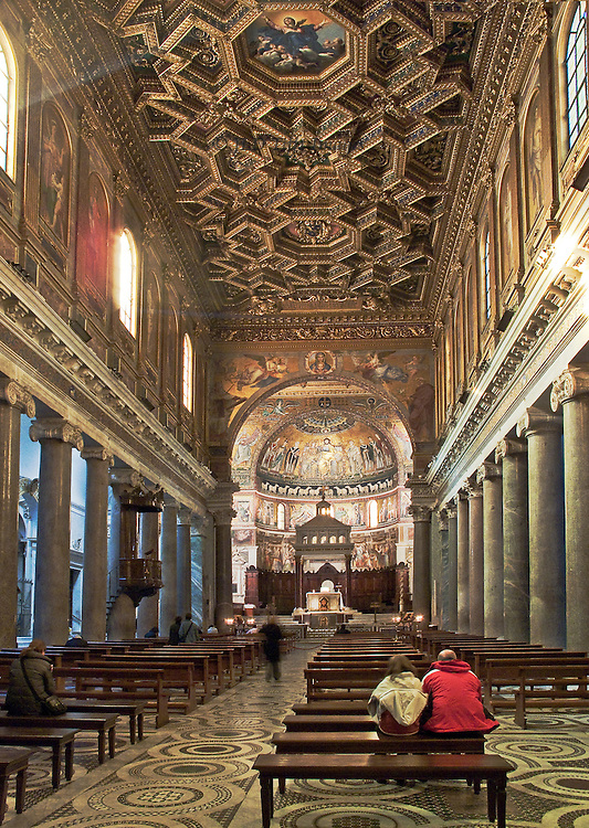 Santa Maria in Trastevere, interior, nave showing basilica form, ceiling, and apse; two visitors seated in contemplation on a bench in the foreground; another walks up the aisle toward the altar.