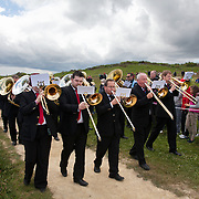 A REQUIEM FOR THE FOGHORN, PERFORMED BY SEVENTY FIVE BRASS PLAYERS, A FOGHORN AND AN ARMADA OF SHIPS<br /> A project by Danish artist, Lise Autogena, in collaboration with Joshua Portway and composer Orlando Gough. <br /> Ships horns from an armada of vessels off-shore, seventy five brass players on-shore and the Souter Lighthouse Foghorn  performed a Foghorn Requiem, an ambitious musical performance to mark the disappearance of the sound of the foghorn from the UK's coastal landscape.<br /> Conducted and controlled from a distance, ships at sea sounded their horns to a musical score, that will took into account landscape and the physical distance of sound. The performance took place by Souter Light House by South Shields, UK with thousands of spectators and more than 50 ships off-shore.<br /> <br /> The brass band walks to the stage along the coast.