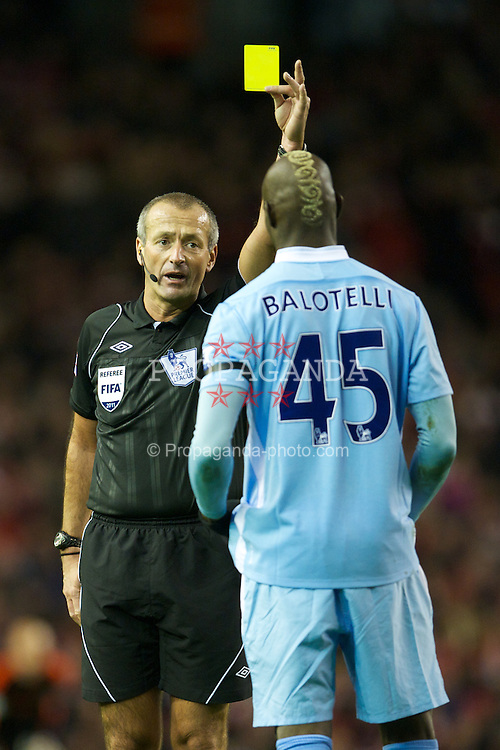 LIVERPOOL, ENGLAND - Sunday, November 27, 2011: Referee Martin Atkinson shows Manchester City's Mario Balotelli the first yellow card, he was later shown a second and sent off, during the Premiership match at Anfield. (Pic by David Rawcliffe/Propaganda)