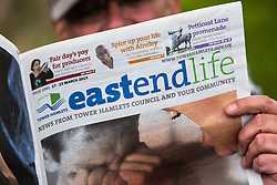 © Licensed to London News Pictures. 19/04/2014. London, UK. A man reads a copy of Tower Hamlets council newspaper, East End Life. Communities minister, Eric Pickles has demanded that five Labour-run London councils, including Tower Hamlets stop publishing free council funded newspapers and has given them a two-week ultimatum to explain why they should not face legal action for breaching publicity code. Photo credit : Vickie Flores/LNP.