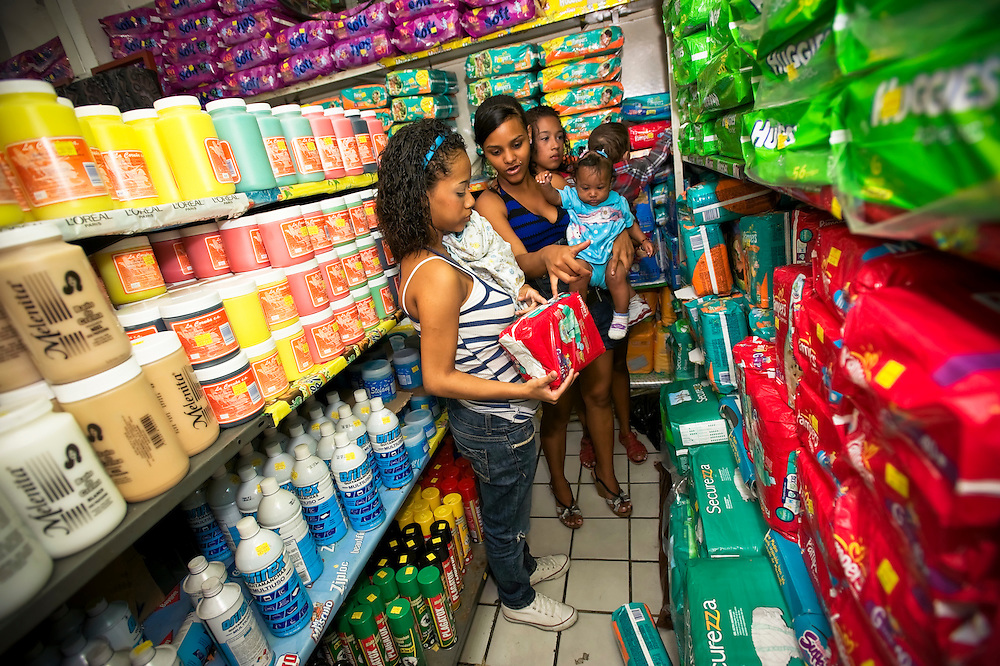 Teenage mother, Diovile Toro, explains how diapers are sized to 15-year-old Yanaifre Acevedo during her first time to buy diapers after giving birth to her newborn son, Dilan.