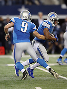 Detroit Lions running back Reggie Bush (21) takes a fourth quarter handoff from Detroit Lions quarterback Matthew Stafford (9) during the NFL week 18 NFC Wild Card postseason football game against the Dallas Cowboys on Sunday, Jan. 4, 2015 in Arlington, Texas. The Cowboys won the game 24-20. ©Paul Anthony Spinelli
