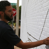 Wendell Brunious of New Orleans spray paints the side of Sneed's Ace Hardware in Oxford Thursday morning
