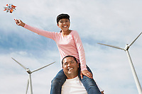 Girl (7-9) sitting on fathers shoulders at wind farm, portrait
