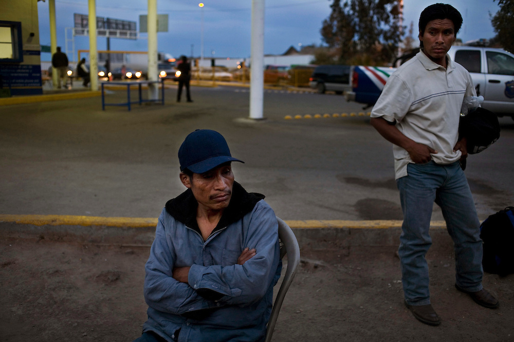 Men sit outside of  a Mexican customs and immigration after being caught by US border patrol illegaly entering the US and being returned to Mexico.