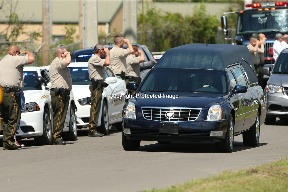 Monroe County Sheriff Deputies salute the hearse as it passes by carrying the late Sergeant Kyle Thomas, as it makes its way to Haughton Memorial Park in Amory for Thomas's graveside service with Military Honors Friday afternoon.