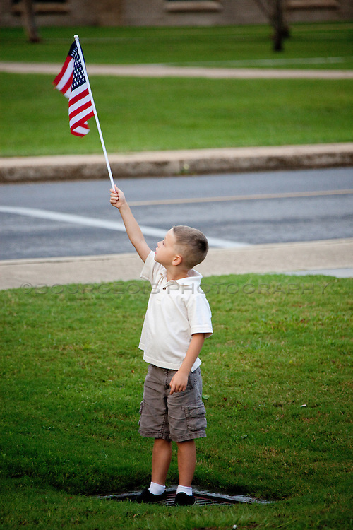 young boy waving holding American flag