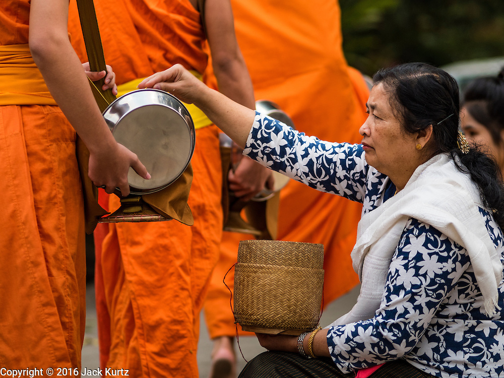 "11 MARCH 2016 - LUANG PRABANG, LAOS:  A Lao woman gives alms to Buddhist monks during the morning tak bat in Luang Prabang. Luang Prabang was named a UNESCO World Heritage Site in 1995. The move saved the city's colonial architecture but the explosion of mass tourism has taken a toll on the city's soul. According to one recent study, a small plot of land that sold for $8,000 three years ago now goes for $120,000. Many longtime residents are selling their homes and moving to small developments around the city. The old homes are then converted to guesthouses, restaurants and spas. The city is famous for the morning ""tak bat,"" or monks' morning alms rounds. Every morning hundreds of Buddhist monks come out before dawn and walk in a silent procession through the city accepting alms from residents. Now, most of the people presenting alms to the monks are tourists, since so many Lao people have moved outside of the city center. About 50,000 people are thought to live in the Luang Prabang area, the city received more than 530,000 tourists in 2014.      PHOTO BY JACK KURTZ"