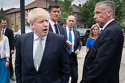 © Licensed to London News Pictures. 25/06/2019. London, UK. Conservative leadership candidate Boris Johnson is surrounded by Metropolitan Police close protection officers as he campaigns in East Sheen, south west London. Mr Johnson is campaigning in various locations in the south east of England today. Photo credit: Peter Macdiarmid/LNP