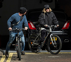 ©  London News Pictures. 10/04/2016. London, UK.  Singer MADONNA (right) leaving her home in central London on her bike, accompanied by security. Madonna was reunited with her son Rocco following a recent court battle over his custody with Madonna's former husband Guy Ritchie. Photo credit: Ben Cawthra/LNP