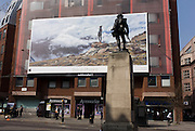 A giant billboard ad for the use of iPhones seen on the side of a central London building, juxtaposed with a WW1 memorial soldier of the Royal Fusiliers.