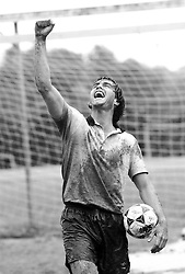 Muddy soccer playing lifting his arm up in triumph
