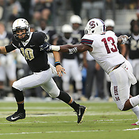 ORLANDO, FL - SEPTEMBER 08:  McKenzie Milton #10 of the UCF Knights runs away from Jarod Jones #13 of the South Carolina State Bulldogs during a football game at Spectrum Stadium on September 8, 2018 in Orlando, Florida. (Photo by Alex Menendez/Getty Images) *** Local Caption *** McKenzie Milton; Jarod Jones