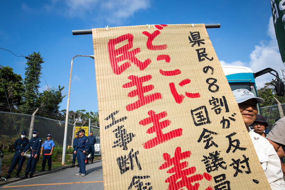 OKINAWA, JAPAN - AUGUST 19 : Anti U.S base protester with sign to protest against the construction of helipads in front of the main gate of U.S. military's Northern Training Area in the village of Higashi, Okinawa Prefecture, on August 19, 2016. Japanese government resume construction of total six helipads in a fragile ten million year old Yanbaru forest that is home to endemic endangered species such as the Okinawan rail and Okinawa wood pecker. (Photo by Richard Atrero de Guzman/NURPhoto)