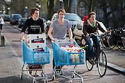 Twee studenten lopen met twee volle winkelwagens van de Albert Heijn met drinken door het centrum van Utrecht.<br /> <br /> Students are walking with groceries, amongst others beer, at the center of Utrecht.