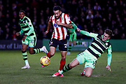 Lincoln City midfielder Nathan Arnold (28) is challenged by Forest Green Rovers midfielder Charlie Cooper (15)  during the EFL Sky Bet League 2 match between Lincoln City and Forest Green Rovers at Sincil Bank, Lincoln, United Kingdom on 30 December 2017. Photo by Simon Davies.
