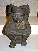 seated figure of Xiuhtecuhtli the Aztec goddess of   Fire. AD 1325-1521 From Mexico. This figure represents Xiuhtecuhtli, the Mexica god of fire. Xiuhtecuhtli is generally represented nude except for a loin cloth, with eyes semi-closed and only two teeth protruding from the corners of his mouth (characteristic of the old god Huehueteotl, with whom he is also identified).