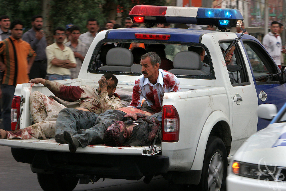 An Iraqi police truck carrying seriously wounded policemen and civilians speeds from the scene of twin car bomb attacks near the offices of the Minister of the Interior in Baghdad, Iraq April 14, 2005.  At least 18 people were killed and 38 wounded in the suicide bomb attack on a busy street in the Karada neighborhood during the morning commute.