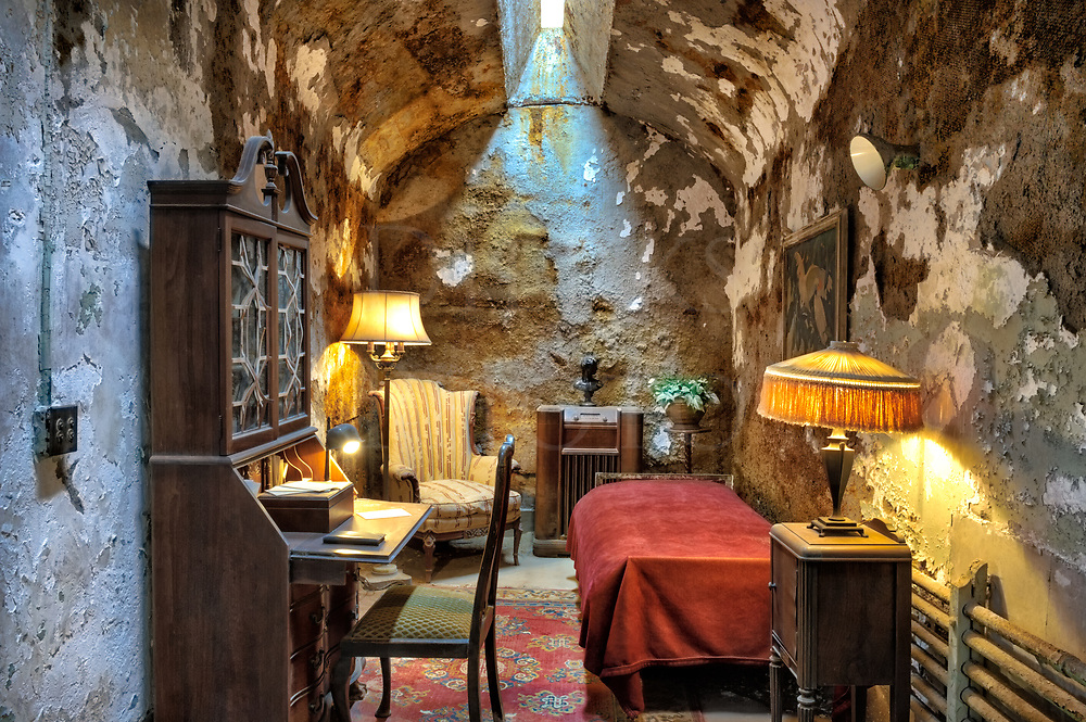 This is Al Capone's prison cell with furnishings during his stay at the Eastern State Penitentiary in Philadelphia, PA.<br /> <br /> In 1929, Big Al had come east on &quot;business&quot; to Atlantic City. On his way back through Philly, he was pursued by rival gangsters who wanted to kill him. To escape, he went up to a street cop and pull open his coat to reveal a pistol. With concealed carry illegal in Pennsylvania at the time, Capone got a year in jail. He ended up here in Eastern State. One of his bodyguards allowed himself to be arrested at the same time and went into prison with Capone to protect him.<br /> <br /> Al did his his short one year stint in the slammer and was released, but as a powerful man that time, enjoyed some obvious privileges while incarcerated, like this furnished room that even had a radio, a comfortable chair, and art on the walls. This is his actual cell somewhat run down nowadays, and the furnishings used approximate the appearance in 1929.