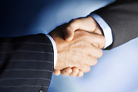 Middle-aged businessmen shaking hands close-up digitally enhanced