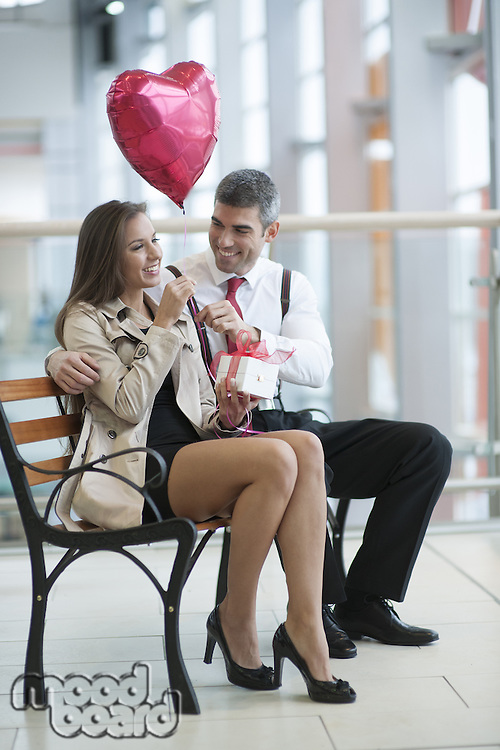 Man gives woman gift and heart shaped balloon