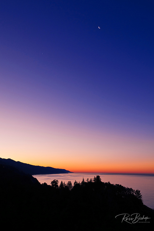 Crescent moon and dawn light over the Big Sur coast, California