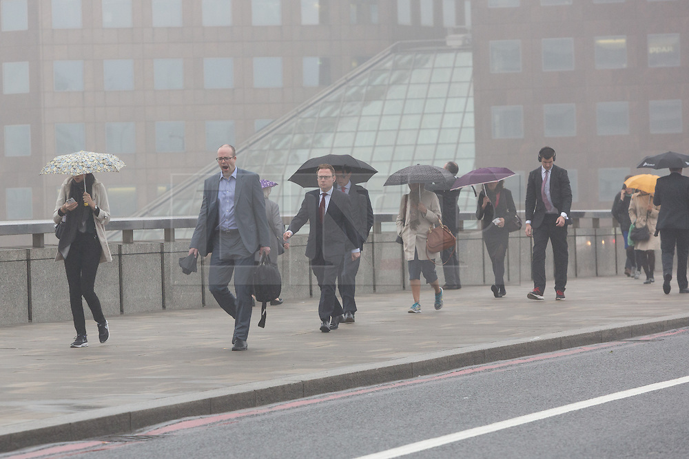 © Licensed to London News Pictures. 11/05/2016. LONDON, UK.  Early morning commuters cross London Bridge in London during foggy and wet weather this morning.  Photo credit: Vickie Flores/LNP