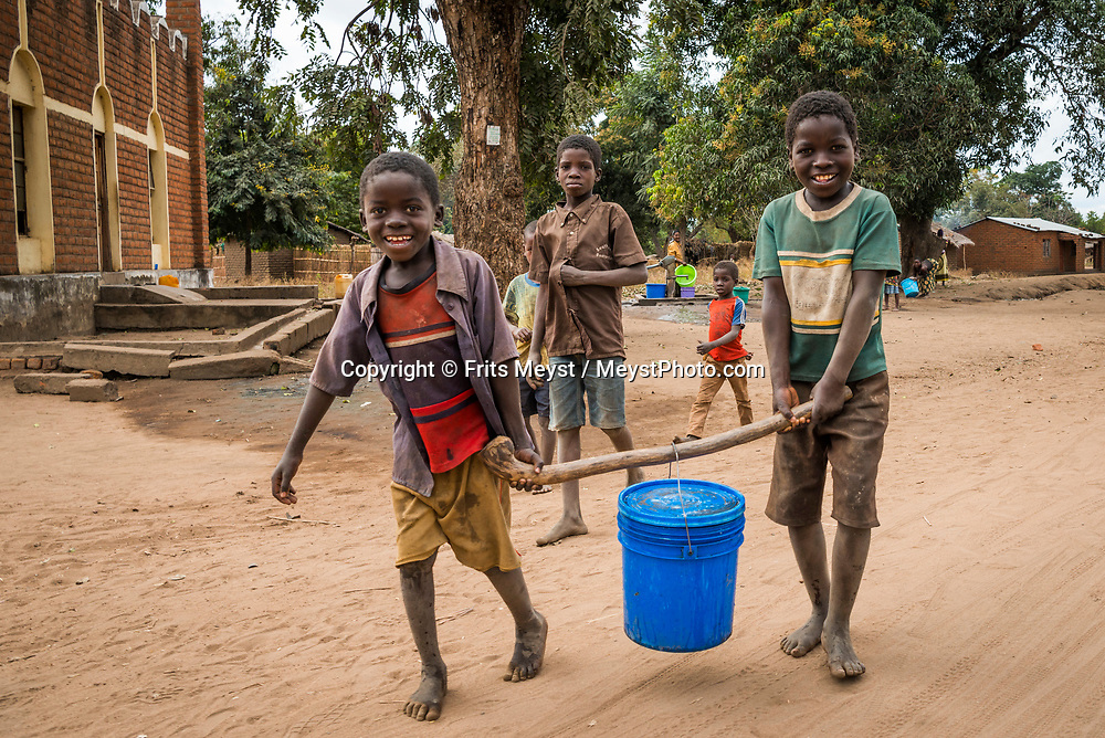 Malawi, July 2017. Women pumping water in the village. Village life in valleys of The Zomba Massif, a mountain of the Shire Highlands in southern Malawi. Malawi is known for its long rift valley and the third largest lake in Africa: Lake Malawi. Malawi is populated with friendly welcoming people, who gave it the name: the warm heart of Africa. In the south the lake make way for a landscape of valleys surrounded by spectacular mountain ranges. Photo by Frits Meyst / MeystPhoto.com