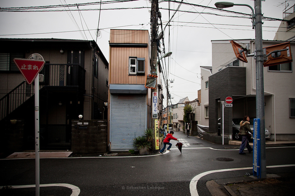 TOKYO, JAPAN, 18 MARCH - Shinagawa  - A child is jumping with umbrella in front of a very small and narrow house - March 2012