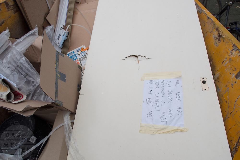 In Utrecht is een briefje op een deur geplakt die door iemand in een afvalcontainer is gegooid met de tekst 'wil deze aso zijn eigen zooi opruimen en niet hier dumpen! Hij gaat niet mee!' Geregeld worden in afvalcontainers bij verbouwingen door anderen afval gedumpt, waardoor de container eerder vol zit en de huurder van de container tegen extra kosten oploopt.